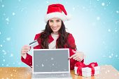 Festive brunette shopping online against blue vignette