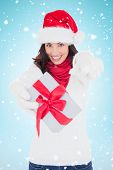 Excited brunette in santa hat giving gift against blue background with vignette