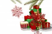 Decorations on tree against green red and gold christmas gifts