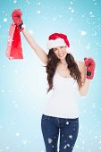 Festive brunette in boxing gloves with shopping bag against blue background with vignette