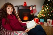 Cheerful redhead reading on the armchair at christmas at home in the living room