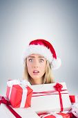Festive blonde holding pile of gifts on vignette background