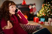 Smiling redhead phoning and gesturing at christmas at hoe in the living room