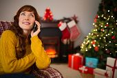 Pretty redhead on the phone at christmas at home in the living room