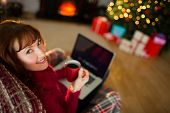 Pretty redhead holding mug of hot drink and laptop at christmas in the living room