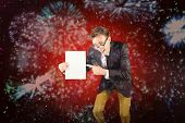 Young geeky businessman holding page against colourful fireworks exploding on black background