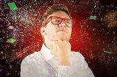 Young geeky businessman with hand on chin against colourful fireworks exploding on black background
