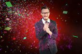 Hipster businessman giving a speech against colourful fireworks exploding on black background