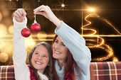 Mother and daughter holding baubles against christmas light design