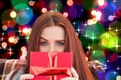 Woman holding gift against light glowing dots design pattern