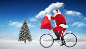 Santa cycling and holding his sack against fir tree in snowy landscape
