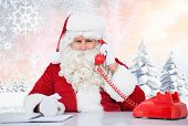 Santa on the phone against snowy landscape with fir trees