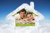 Two friends lying together on a blanket while smiling against blue sky over clouds