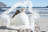 Couple sitting on the beach under blanket looking out to sea against house outline in clouds