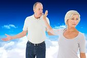 Older couple having an argument against bright blue sky over clouds