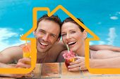 Beautiful couple drinking cocktails in the swimming pool against house outline