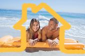 Cheerful cute couple in swimsuit lying on the beach against house outline