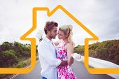 Cute couple standing on the road hugging against house outline