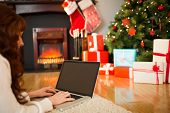 Redhead woman lying on floor using laptop at christmas at home in the living room