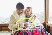 Loving couple in winter wear with cups against window against house outline