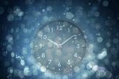 black clock against blue abstract light spot design