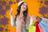 Beauty brunette holding credit card and shopping bags against blurred snowflake design