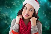 Happy brunette in winter clothes smiling at camera against blurred christmas background