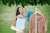 Smiling woman shopping against blurred fir tree branches on wood