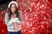Pretty brunette in winter clothes blowing against blurred lights