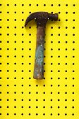 Hammer Hangs On Two Hooks From Yellow Peg Board