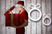 Festive blonde opening a gift against blurred christmas decorations on wood