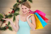 Smiling woman presenting while holding shopping bags against blurred holly on wood