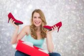 Smiling woman holding up her new shoes against blurred lights