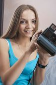 Portrait Of Caucasian Blond Female Wearing Braces Posing With Photocamera