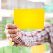 Man Holding Yellow Sign At Supermarket