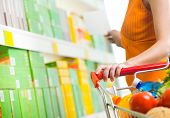 picture of grocery cart  - Young woman taking products from shelf at supermarket and holding a shopping cart - JPG