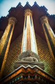 stock photo of budha  - Statue of budha in a thai temple with three golden pilars - JPG