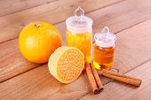 Bottles of essential oil and bath salt with orange, bar of soap and cinnamon on wooden background