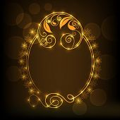 Beautiful floral design decorated shiny golden frame in oval shape on brown background.