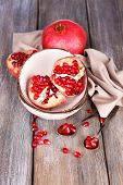 Beautiful composition with juicy  pomegranates, on old wooden table