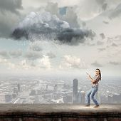 Young woman in casual catching cloud with rope