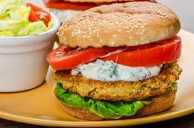 stock photo of veggie burger  - Vegetarian chickpea burger tomato and dip of herbs garlic and yogurt and salad with cherry tomatoes - JPG