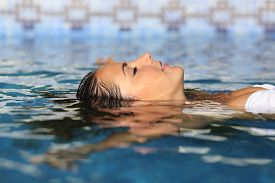 foto of floating  - Profile of a beauty relaxed woman face floating in water of a pool enjoying vacations - JPG