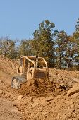 picture of bulldozer  - Large bulldozer moving rock and soil for fill for a new commercial development road construction project - JPG