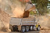 stock photo of track-hoe  - Large track hoe excavator filling a dump truck with rock and soil for fill for a new commercial development road construction project - JPG