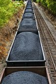 image of train track  - Vertical shot of a very long coal train full of coals sitting on tracks ready to go - JPG