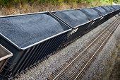 pic of train track  - Horizontal shot at an angle of a coal train full of coal on train tracks - JPG