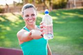 picture of bottle water  - female athlete holding a bottle of water in front of her with the focus on the water bottle - JPG