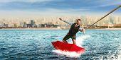 foto of ski boat  - Businessman on water skis in umbrella - JPG