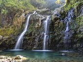 stock photo of fall trees  - Tripple Waterfall called Upper Waikuni Falls or Three Bear Falls of the Wailua Nui Stream along the Road to Hana on Maui Island in Hawaii - JPG